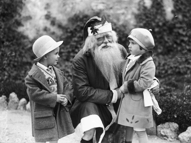 Santa Claus pauses from his toy-making demonstration to visit with Roger Martin and Eloise Jones, 1928.  (MS 359: L-0720-A)