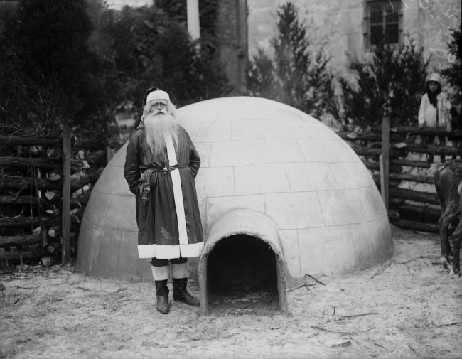 Santa Claus stands outside his igloo in front of the Alamo, 1928.  His reindeer are partly visible on far right.  (MS 359: L-0720-M)