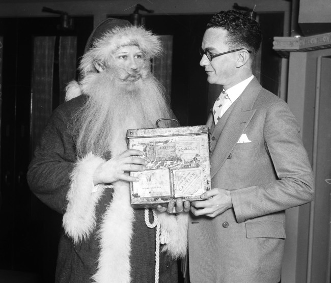 "Santa Claus hands Raymond Jones, manager of the Princess Theater, a copy of the movie ""Santa Claus,"" 1926.  The film, documenting Santa's activities at the North Pole from one Christmas to the next, was featured daily for one week at the theater on Houston Street.  (MS 359: L-0720-I)"