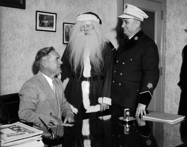 Santa Claus joins Jack White (left), manager of Plaza Hotel, and Fire Chief J.G. Sarran as they plan an event to acquire toys to distribute to needy children on Christmas Day, 1935.  (MS 359: L-0845-C)