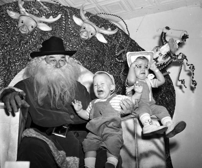 Charles Malven and Mary Reams are frightened of Santa Claus (W.D. Taylor) and his ten-gallon hat, 1947.  (MS 359: L-3494-A)