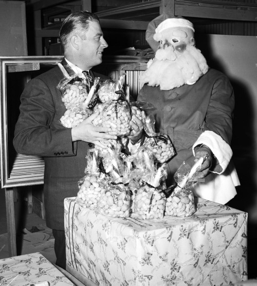 Harry Jersig, president of Lone Star Brewing Company, and Santa Claus (Jimmy Faulkner) with Christmas gifts to be distributed at the annual dinner for the local newsboys, 1948.  (MS 359: L-3628-F)