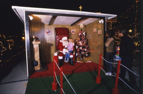 Santa Claus listens to Christmas wishes in a suburban neighborhood, 1988.  (MS 359: L-7172-45-23)