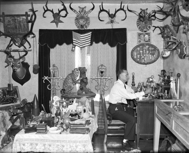 "Fire Chief J. G. Sarran poses with his antique weapons, hunting trophies, and an assortment of odd curios that are displayed in his special room that is reminiscent of the European Wunderkammer (""wonder-room""), November 1932.  (MS 359: L-0332-F)"