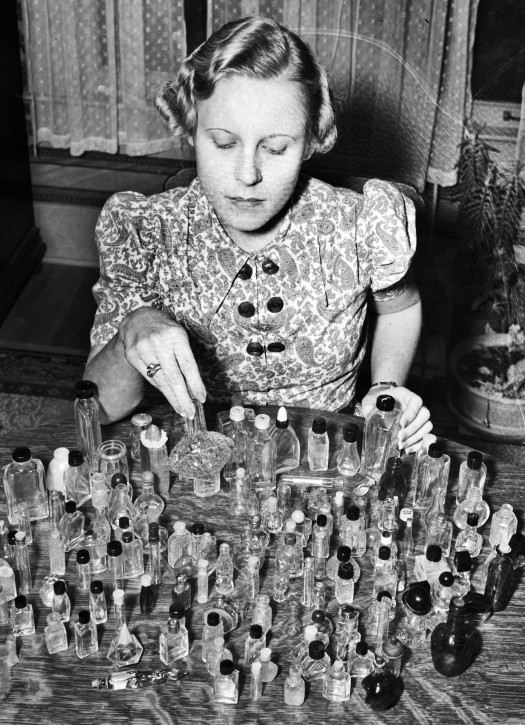 Mildred Fields with examples of the many bottles she has collected since she began the hobby at age ten, November 1937.  (MS 359:  L-1696-F)