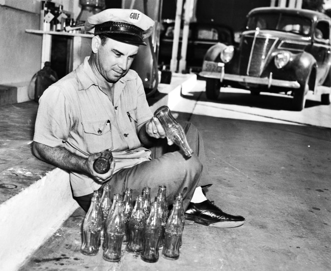 Henry Willis displays some of the Coca-Cola bottles from his large collection, each embossed with the name of a different city where the drink was bottled, August 1939.  (MS 359:  L-2224-G)