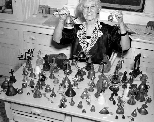 Mrs. Albert Friedrich rings two bells from her collection composed of over a 100 examples from all over the world, many purchased during her travels, April 1940.  (MS 359:  L-2435-C)