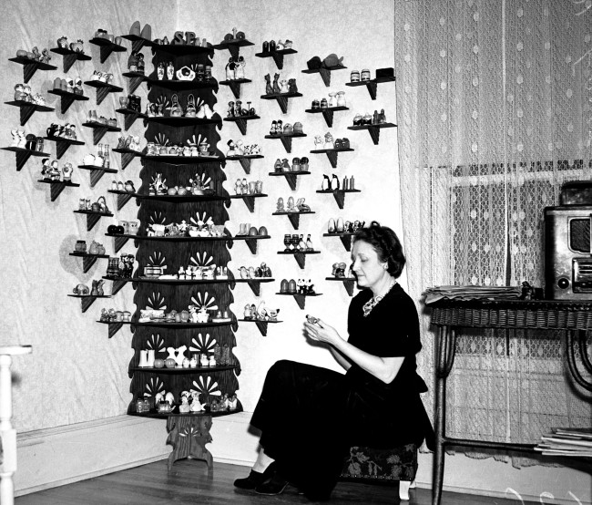Mrs. A. L. Ernst sits next to her display of 155 pairs of salt and pepper shakers, most given to her by friends, December 1940.  (MS 359:  L-2626-C)