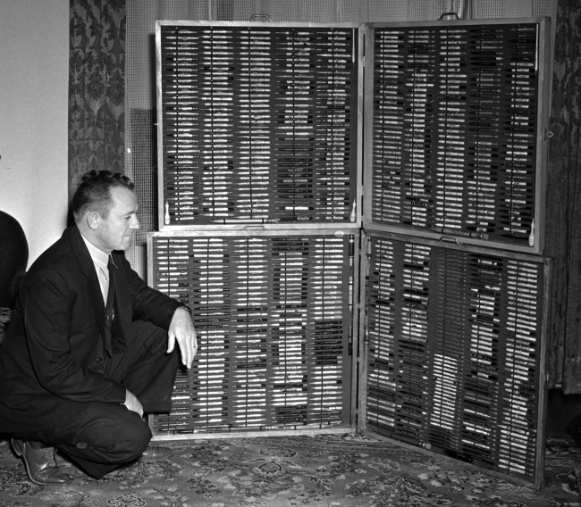L. Harold Shugart, shipping clerk at the Texas Company, with his collection of mechanical advertising pencils, some with a sample of the company product mounted in the top, January 1941.  (MS 359:  L-2645-G)
