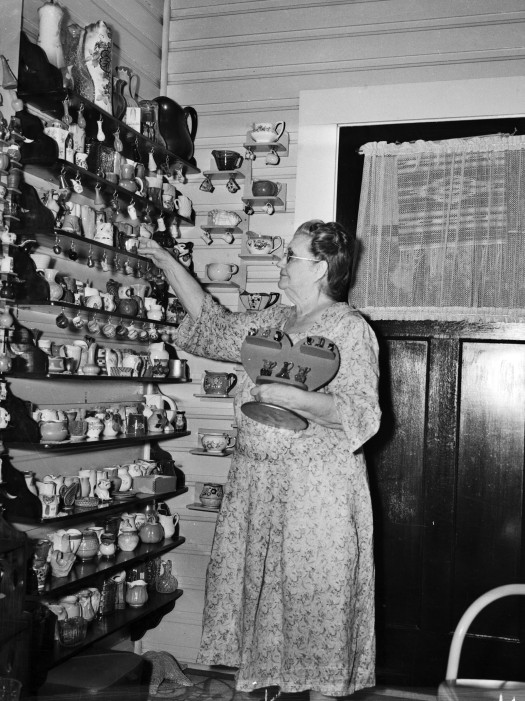 Mary Templeton stands in a specially-built room to house her collection of over 1500 pitchers, primarily gifts from friends or tradesmen, August 1941.  (MS 359: L-2807-B)