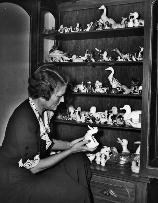 Mrs. Ernst Schuchard examines a ceramic duck figurine from the collection in her home on King William Street, February 1942.  (MS 359:  L-2907-G)