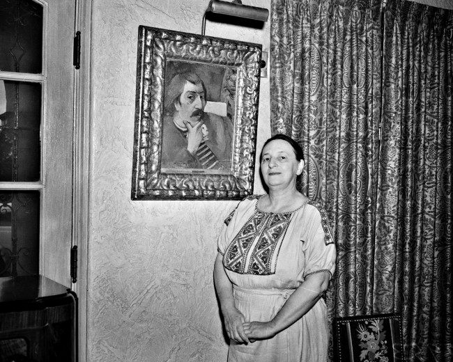 Marion Koogler McNay stands next to a self-portrait of Paul Gaugin, one of the many significant works of art in her home that later became the McNay Art Museum, May 1942.  (MS 359:  L-2953-C)