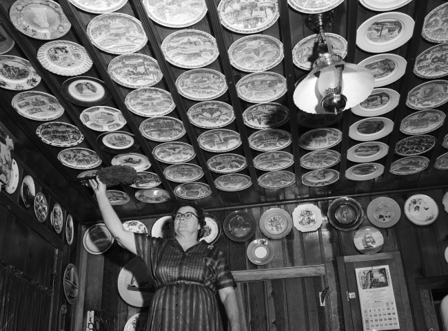 Vennette Hamel, manager of Schaper's Food Market, dusts collection of souvenir plates in her home on East Schley Street, January 1954.  (MS 359:  L-4639-C)
