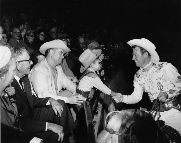 "Rex Allen pauses to greet a fan as he circles the arena on KoKo,"" the miracle horse of the movies,"" during the rodeo entertainment program, 1953.  (MS 355:  Z-2469-B-22738)"