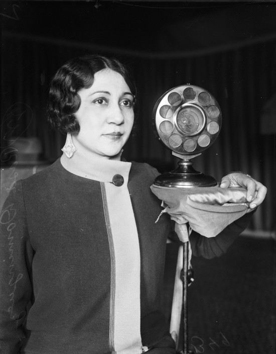"Rosa Dominguez, coloratura soprano, stands next to WCAR microphone at the time she was performing songs of her native Mexico, November 1925.  (MS 359:  L-0349-A).  Dominguez later appeared in New York and regularly on Border Radio, where she received the title ""The Mexican Nightingale."""