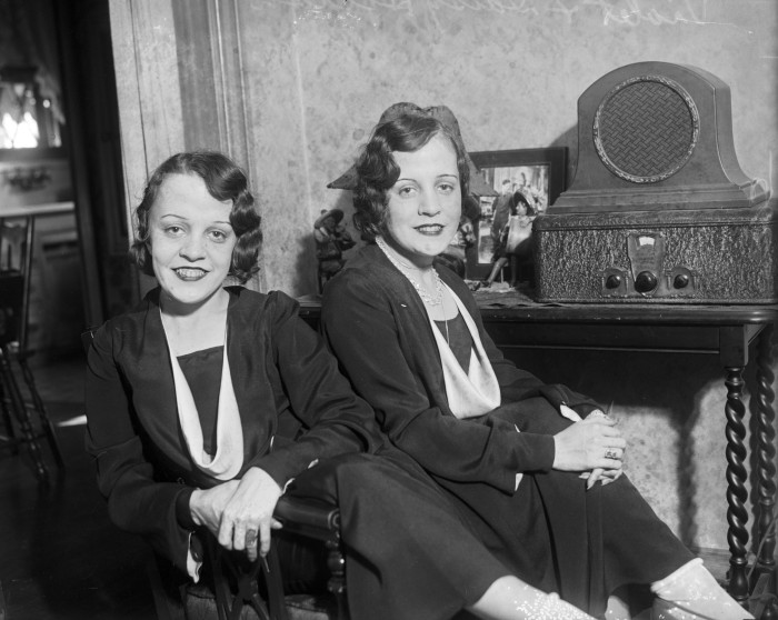 Violet Hilton (left), a saxophonist, and Daisy Hilton, a violinist, seated in their home on Vance Jackson Road, January 1931.  (MS 359:  L-395-I).  The Hilton Siamese twins (1908-1969) toured the country performing in sideshows, vaudeville, and cabarets during the 1920s and 30s.