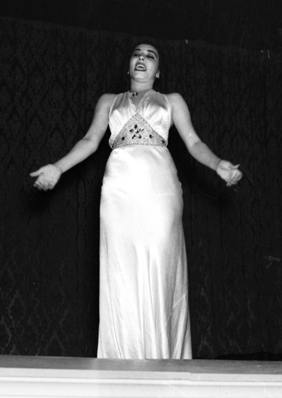 "Eva Garza, former student at Lanier High School, sings on stage at El Nacional Theater on East Commerce Street, May 1939.  (MS 359:  L-1583-A).  By the 1940s, Garza (1917-1966) was appearing weekly in New York for CBS Radio's ""Viva America"" and on the ""Voice of America.""  She was known to U.S. soldiers as ""the Sweetheart of the Americas."""