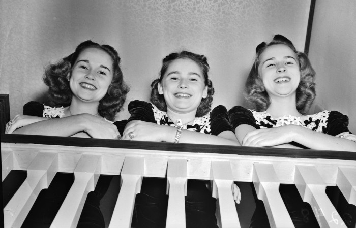 "The Read Sisters (left to right) Floy, Donald Ruth, and Martha pose on the stairway of their home on Post Avenue at the time they sang weekly on WOAI Radio's ""Saturday Night Parade,"" September 1939.  (MS 359: L-2248-C).  The trio, originally from Corpus Christi, later toured the country with Olsen and Johnson's Hellzapoppin' revue."