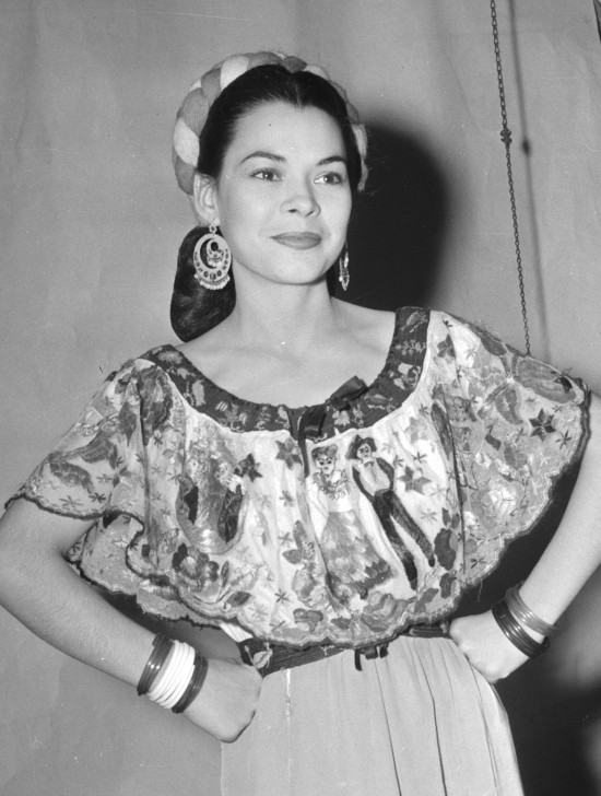 "Rosita Fernandez (Almaguer) poses in a Mexican dress shortly before she sang Mexican ballads in a show at La Villita, July 1944.  (MS 359:  L-3132-A).  Fernandez (1919-2006) became a local radio star in the early 1930s, and later appeared on television and in movies.  Lady Bird Johnson gave her the title ""San Antonio's First Lady of Song.""  The Rosita Fernandez Collection is housed in UTSA Special Collections Main Campus:   http://www.lib.utexas.edu/taro/utsa/00043/utsa-00043.html"