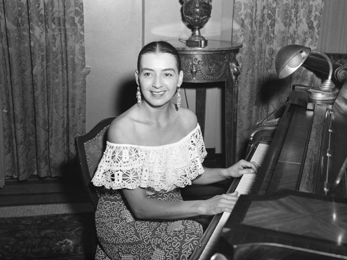 Bea Morin (Svercel) seated at piano during a return visit to play in the St. Anthony Hotel lobby, where she played regularly for over a decade as a young woman, July 1952.  (MS 359:  L-4377-A).  Morin (1910-2007), a regular local radio performer in the late 1930s and early 1940s, moved with her husband to New York and played organ for live television programs in the 1950s.