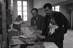 Dr. Patenaude, Dr. Almaraz and Archivist Thelma Gavin review a bound volume in poor condition, student with Ernest Malina, Jr. works in background. MS 27: txsau_ms00027_4-18-77-3-36a