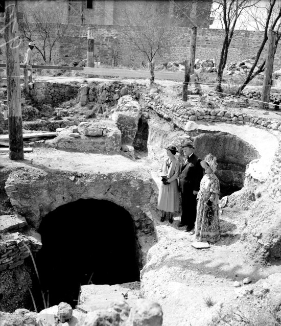 Group looks at excavated ruins of the Mission San Jose mill shortly before the San Antonio Conservation Society began restoration, March 1936.  On left is Mrs. Conn Milburn, of the Conservation Society, with Erhard Guenther, president of Pioneer Flour Mills, and Mrs. J.K. Beretta, of the Society of Colonial Dames.  The Colonial Dames contributed funds for the project and Pioneer Flour Mills researched and built the mill machinery.  (MS 359: L-0972-L)