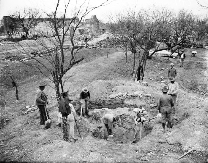 Central Relief Committee workers uncover stone foundations, later determined to be the long-forgotten mill, near the north wall of the mission compound.  The granary is in background on left, January 1933.  (MS 359:  L-1424-E)