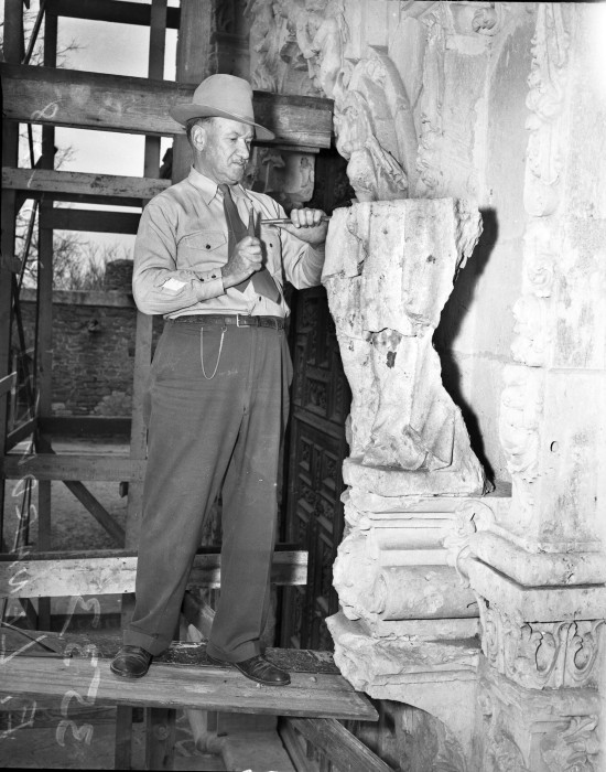 Sculptor Eraclito Lenarduzzi, owner of Southern Monument Company in Houston, begins work of replacing missing portions of the statues on the richly carved church façade, May 1948.  (MS 359: L-3533-F)