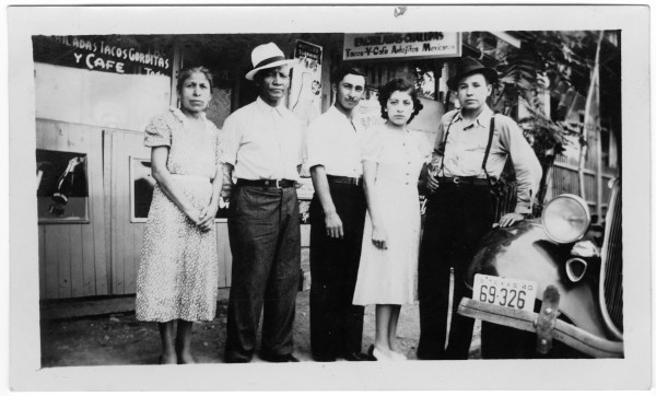 Newlyweds Pedro and Jovita Ortiz pose between her parents, Francisca and Magdaleno de la Rosa, and her uncle, Ausencio Bernal, May 17, 1940.  They are standing outside De la Rosa Café, 621 South Laredo Street.  (MS 454: 115-0160)