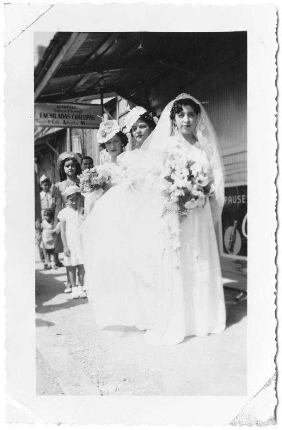 Jovita de la Rosa and her wedding party outside the family business and residence shortly before her marriage to Pedro Ortiz at nearby Immaculate Heart of Mary Catholic Church, May 12, 1940.  (MS 454: 115-0161)
