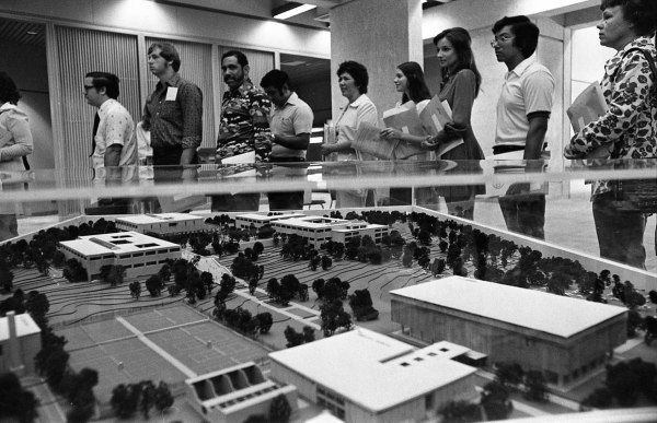 A line of waiting students wraps around an architectural model of the not-quite-finished campus.