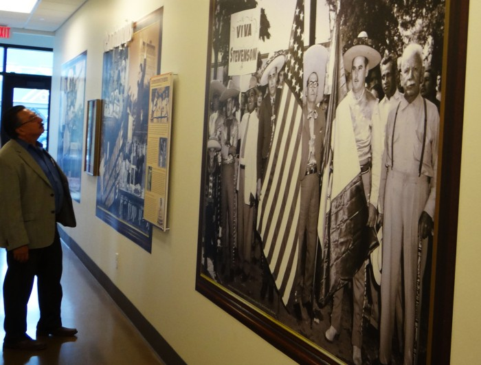 Visitor looks at murals and interpretive panels in corridor of purchasing department.