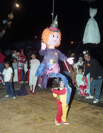 Valerie Garcia prepares to swing at a piñata at Halloween party in the Lavaca neighborhood, 1989. (San Antonio Express-News Collection, MS 360: EN- 1989-10-31-9)