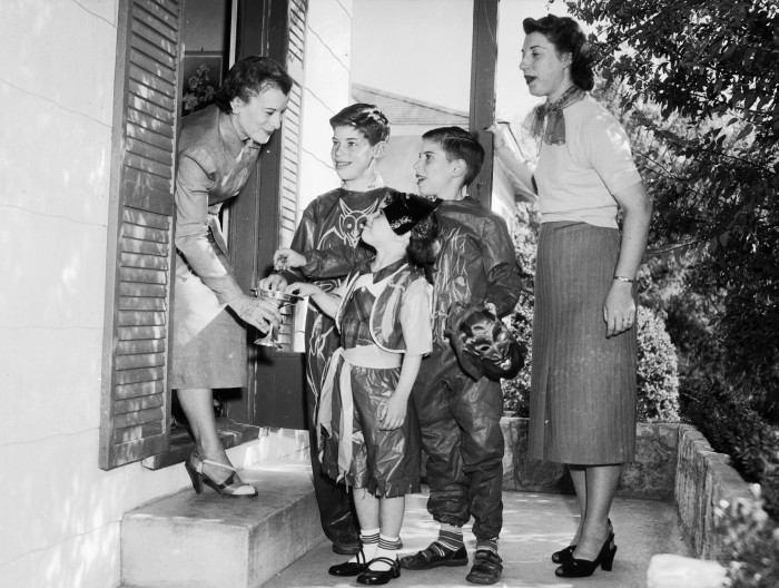 Staged photo illustrating trick-or-treating. Mrs. Giles Hawley gives candy to her grandchildren, the children of Imogene Hawley Moench (right), 1952. (San Antonio Light Collection, MS 359: L-4401-D)