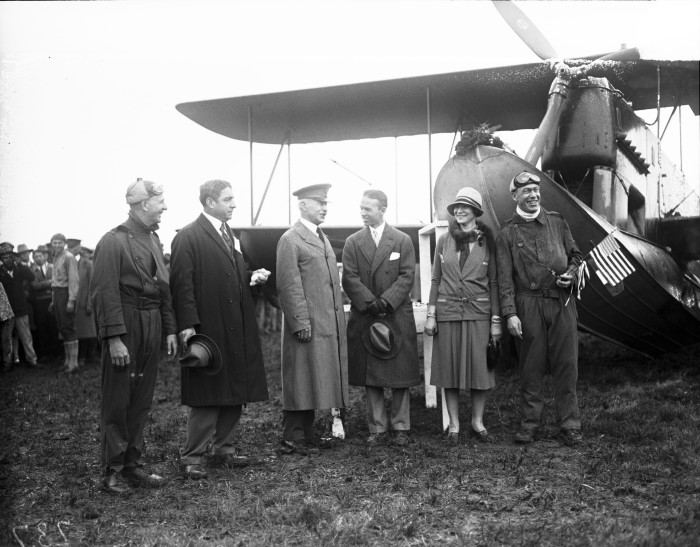 Maj. Gen. Mason Patrick (third from left) talks to Grover Loening following the christening services and send-off speeches held during intermittent drizzle, Duncan Field, December 20, 1926. At about that time, word was received that the flight would be delayed due to the muddy field. The planes were towed to neighboring Kelly Field for takeoff the following day from a paved runway.