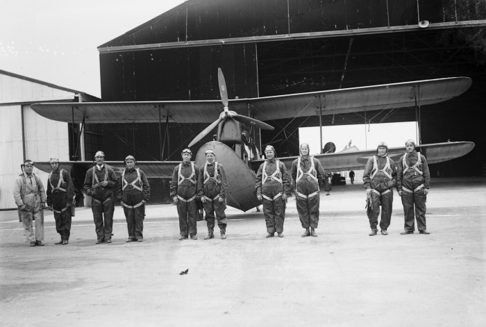 "The pilots pause before making practice flights and landings on Medina Lake, Duncan Field, December 17, 1926. (Left to right) Capt. Arthur McDaniel and Lt. Charles Robinson, ""San Antonio"" pilots; Capt. Clinton Woolsey and Lt. John Benton, ""Detroit"" pilots; Maj. Herbert Dargue and Lt. Ennis Whitehead, flagship ""New York"" pilots; Lt. Bernard Thompson and Lt. Leonard Weddington, ""St. Louis"" pilots; and Capt. Ira Eaker and Lt. Muir Fairchild, ""San Francisco"" pilots. (MS 359: L-0738-B)"