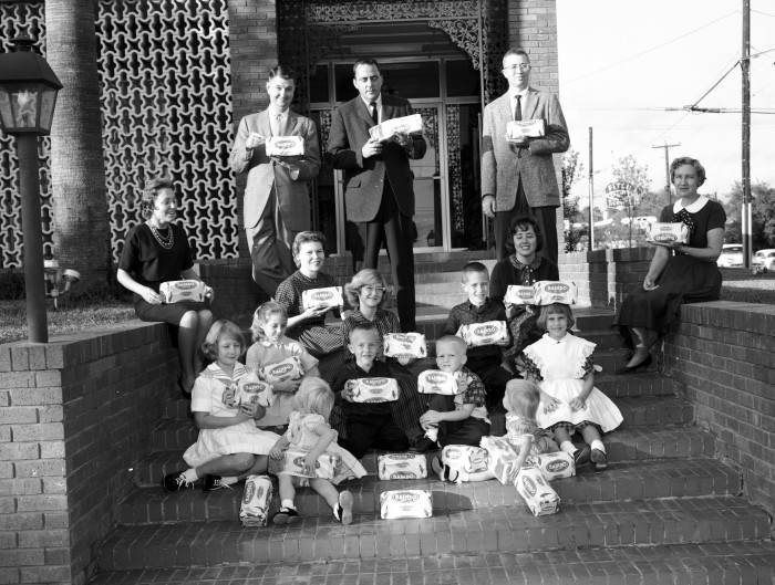 Fraser-Wiggins-Collins and Steckly Advertising Agency owners and models with loaves of bread made by client Rainbo Baking Company. Taken outside the agency offices at 147 East Mistletoe Avenue, November 1962. (MS 355: Z-0751-A-33279)