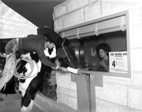 KTSA Television Station representative visits the drive-up window at First National Bank, 213 West Commerce Street, 1960s. (MS 355: 0753-E-01)