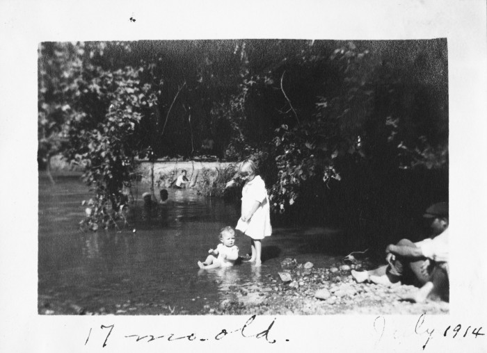 Charles H. Brewster, Jr. sits at the edge of the San Antonio River, July 1914. (MS458: 115-0345)
