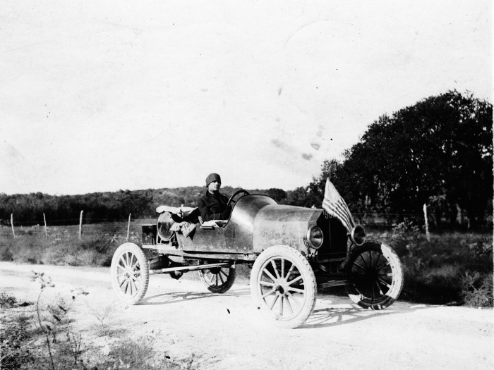 """Dutch,"" a family friend, in his car ""Pathfinder"" on a road in the Texas Hill Country, 1916. (MS458: 115-0443)"
