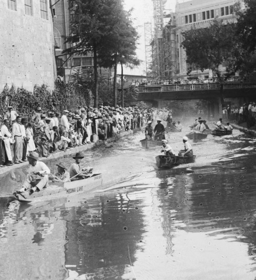 "Shortly after the beginning of the race, the eight boats head downstream from the Houston Street Bridge on the morning of September 6, 1926. In the lead are the Dean Brothers in ""Canvasback,"" a skiff with wooden sides and a canvas bottom. Texas Theater under construction at upper right. (MS 359: L-0676-E)."