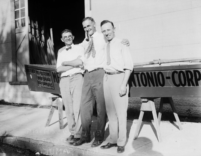 "(L. to r.) Bill Busching, skipper, Bob Edgar, and Ray Samuels, pose with their 300 pound skiff ""King Fisher,"" outside San Antonio Planing Mill, September 1926. (MS 359: L-0676-F)"