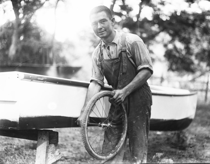 "Tom Dean, Jr., first mate of the ""Potchernick-Dean,"" shows one of the wheels he'll have in the skiff for use in shallow water. (MS 359: L-0686-E)"
