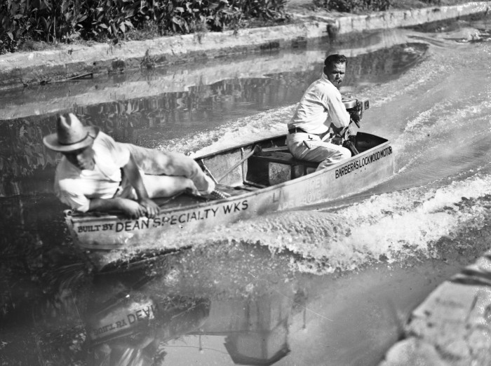 "Roscoe K. Blaine (left) and Riley Harris in the San Antonio Public Service Company entry, the ""Live Wire,"" travel through a downtown stretch of the river shortly after beginning of the race. (MS 359: L-0804-A)"