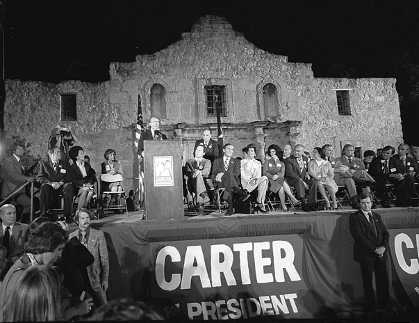 "Jimmy Carter speaks at the ""grand finale"" of the local Democratic Party campaign, October 30, 1976. Joining him on the podium are all the state's most prominent Democrats, including Gov. Dolph Briscoe, Sen. Lloyd Bensen, and Rep. Henry B. Gonzalez. Another group of Carter supporters objected to the Alamo as a site for political gatherings and held a simultaneous rally at HemisFair Plaza. (MS 360: E-0039-200-27)"