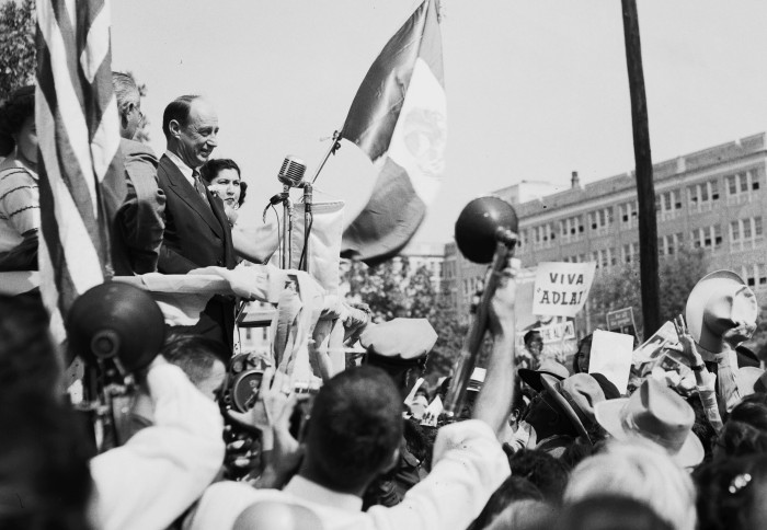 Illinois Governor Adlai Stevenson, Democratic Party nominee for President, stands between the U.S. and Mexican flags at a rally in Milam Park, October 18, 1952. Stevenson's speech paid tribute to the heritage and contributions made to the United States by Latin-American Texans. From there he traveled to Alamo Plaza to deliver another speech. (San Antonio Light Collection, MS 359: L-4416-C-12)