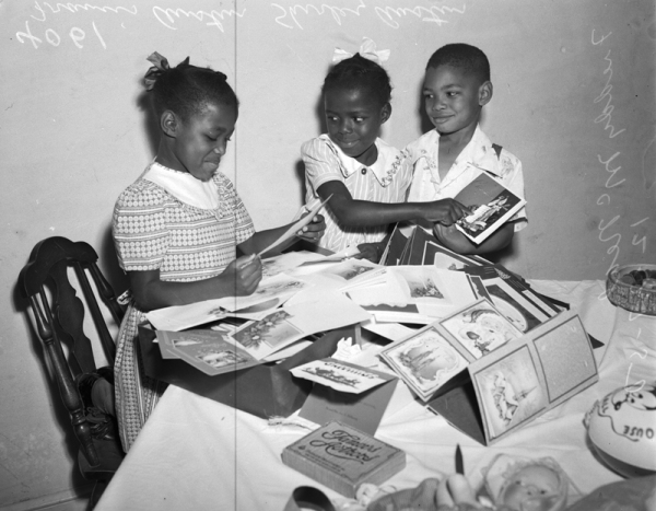 Francis Austin, Shirley Austin, and Freddy McNeal with a pile of holiday cards. December 1950.