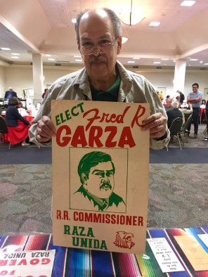 Fred Garza holding one of his own posters from his collection