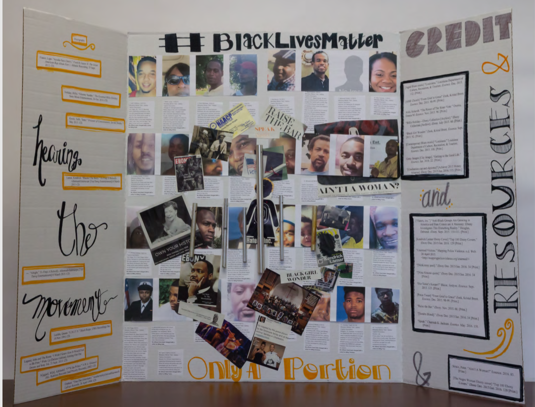 Photo shows a trifold poster with photos of those affected by police violence and the #blacklivesmatter slogan as well as more unreadable text boxes in orange and black