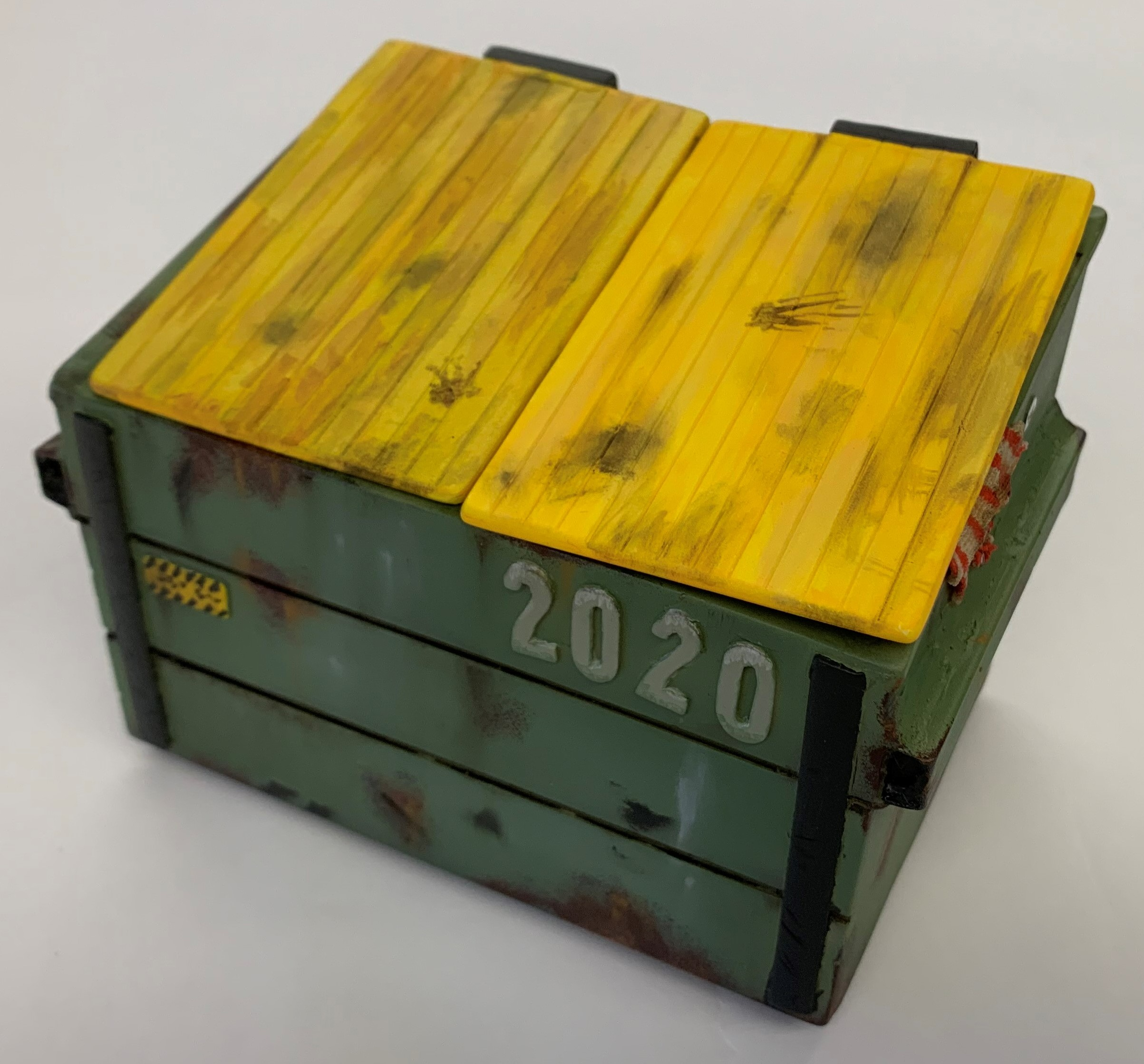a green, resin-cast dumpster with yellow lids and 2020 is printed on the front